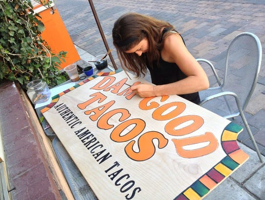 Ali Hatcher paints the sign for Dam Good Tacos. The