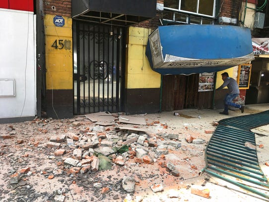 A man enters a damaged building after an earthquake