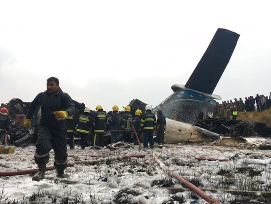 Nepalese rescuers stand near a passenger plane from