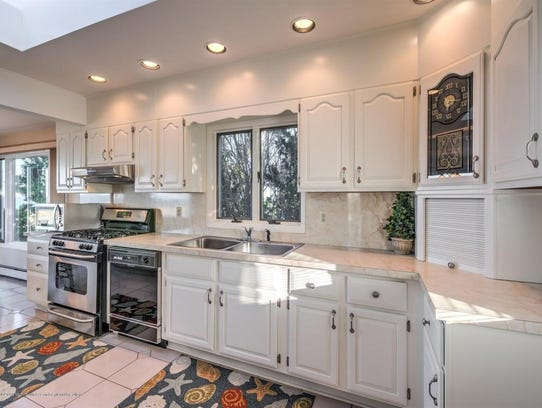 The open concept kitchen features white cabinetry with recessed lighting.