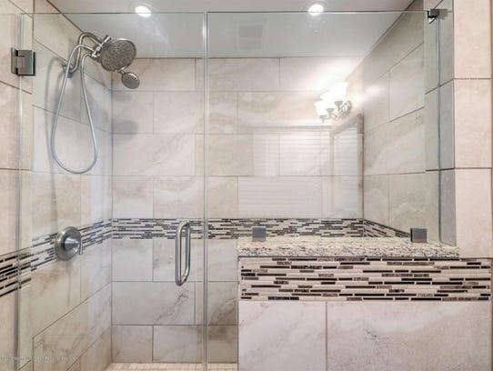 The bathroom has a  glass shower door, ceramic tile, and detachable shower head.