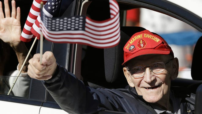 Eugene Slaske, 95 years old, who fought with the Marines in the South Pacific during WWII rides with the War Dogs contingent during the Veterans Day Parade downtown on Saturday. November 5.