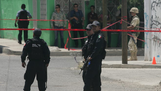 Mexican federal police stand guard at a crime scene in Juárez.