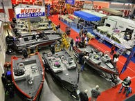 Show attendees look through a display of boats from Westre's Marine & Sport during the Sportsmen's Show Saturday at River's Edge Convention Center.