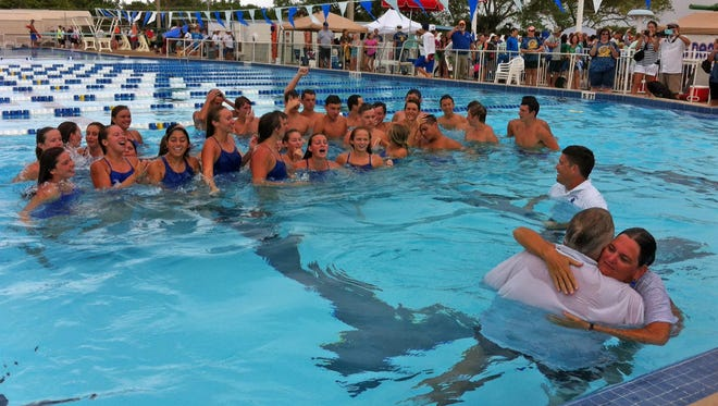Titusville High's girls and boys swimming teams celebrates after each squad won their respective Cape Coast Conference meets in Cocoa Beach on Friday.