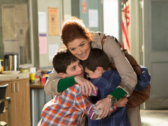 """This image released by NBC shows Charlie Reina, left, Debra Messing and Vincent Reina, right, in a scene from """"The Mysteries of Laura,"""" premiering Sept. 24. (AP Photo/NBC, KC Bailey)"""