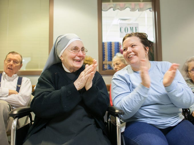 Sister Genevieve Fitzpatrick and Kelly Mahoney clap to live music played by the band.  Nov., 24, 2013