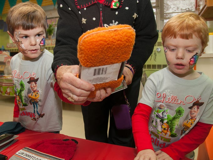 Alexander Sims, left, and his brother Harrison Sims pick out presents for their family in a gift shop where everything can be purchased for one dollar. Dec., 14, 2013