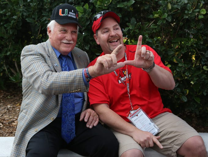 "Former U of L and Miami coach Howard Schnellenberger, left, and U of L fan Brian Eschman show off their ""L"" at a pep rally for U of L the day before Louisville plays Miami in the Russell Athletic Bowl in Orlando, Fla. Dec. 27, 2013."