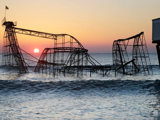 This Feb. 25, 2013 file photo shows the sun rising in Seaside Heights, N.J., behind the Jet Star Roller Coaster which had been sitting in the ocean after part of the Casino Pier was destroyed during Superstorm Sandy.