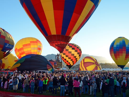 A balloon lifts off over the crowd in the early morning during the annual Albuquerque International Balloon Fiesta in Albuquerque.