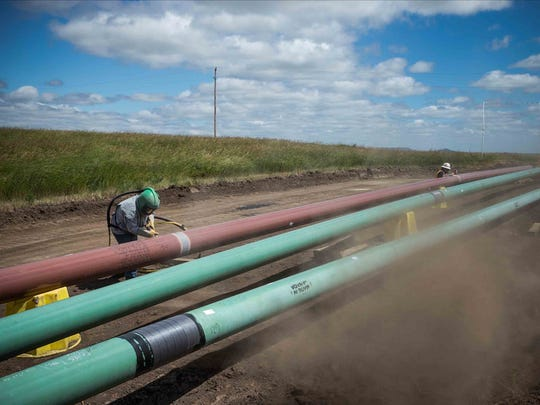 A construction worker specializing in pipe-laying sandblasts a section of pipeline on July 25, 2013 outside Watford City, N.D. Enbridge Energy Co. sought to build an oil pipeline stretching from North Dakota to northwestern Wisconsin.