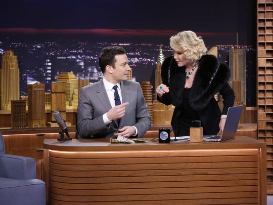 """In this Monday, Feb. 17, 2014 photo provided by NBC, Joan Rivers appears with Jimmy Fallon during his debut on """"The Tonight Show"""" in New York. Rivers, the raucous, acid-tongued comedian who crashed the male-dominated realm of late-night talk shows and turned Hollywood red carpets into danger zones for badly dressed celebrities,  died Thursday, Sept. 4, 2014. She was 81. Rivers was hospitalized Aug. 28, after going into cardiac arrest at a doctor's office. (AP Photo/NBC, Lloyd Bishop, File)"""