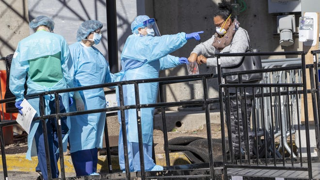 A member of the Brooklyn Hospital Center helps a person who was just tested for COVID-19 put an object in a biohazard bag in March in New York.