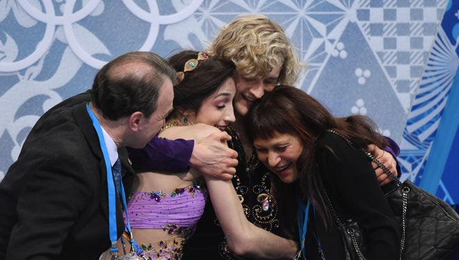 Meryl Davis and Charlie White (USA) receive hugs in the kiss and cry area after receiving their scores during the ice dance free dance program.