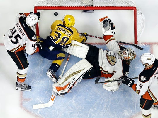 Anaheim Ducks goalie John Gibson (36) and Nashville Predators left wing Viktor Arvidsson (38), of Sweden, fall to the ice as a shot by Nashville Predators left wing Filip Forsberg, of Sweden, not shown, gets past for a goal during the third period in Game 3 of the Western Conference final in the NHL hockey Stanley Cup playoffs Tuesday, May 16, 2017, in Nashville, Tenn. The Predators won 2-1 and lead the series 2-1. Also defending for the Ducks are Sami Vatanen (45), of Finland, and Cam Fowler (4). (AP Photo/Mark Humphrey)