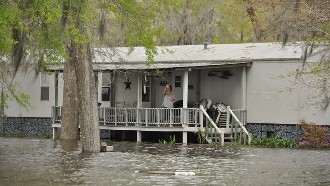 A Grant Parish woman waves from her porch Thursday as water from Nantachie Lake, which is being flooded by Red River backwash, creeps up closer to her home.