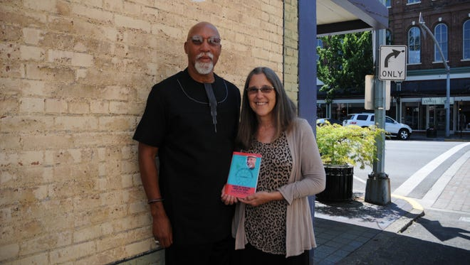 The Rev. Rodney Alexander and his wife, Teri, show off his book about the pllight of the global spiritual community.