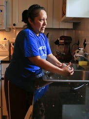 Maria Diaz works in the kitchen of a cleaning client