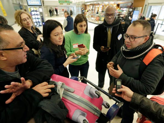 Munther Alaskry, right, is interviewed by members of the lawyers group NoBanJFK as he arrives at New York's JFK International Airport, in New York, Friday, Feb. 3, 2017. Alaskry and his family arrived at New York's Kennedy Airport after the Trump administration reversed course and said he and other interpreters who supported the U.S. military could come to America. They spent nearly a week in limbo in Baghdad, thinking their hopes of starting a new life free from death threats had been shattered.