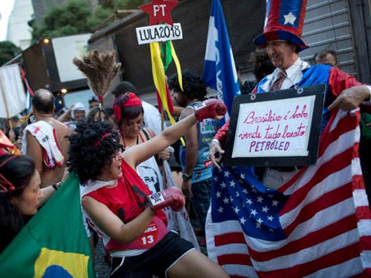 "A reveler pretends to hit a man representing the United States who holds a sign that reads in Portuguese: ""Brazilian is fooling, selling everything cheap. Oil"" during the ""Out Temer"" carnival street party in Rio de Janeiro, Brazil, Friday, Feb. 24, 2017. Merrymakers took to the streets to protest Brazil's President Michel Temer."