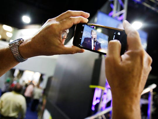 Alan Hasman, of Rochester, N.Y., takes a photo of a television in the exhibition hall broadcasting President Donald Trump speaking at the National Rifle Association's annual convention in Atlanta, Friday, April 28, 2017.