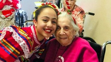 Red Mountain Middle School eighth grader Crystal Sanchez gets a hug from Mimbres Memorial Nursing Home resident Antoinette Weatherwax during a ballet folklorico performance put on Raquel Calles' ESL students on Tuesday, Dec. 19.