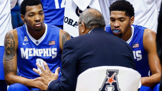 University of Memphis brothers K.J. Lawson (left) and Dedric Lawson (right) listen to head coach Tubby Smith during a timeout during second half action against Central Florida University at the American Athletic Conference tournament game in Hartford, Conn.