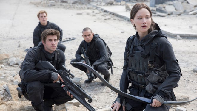 """This photo provided by Lionsgate shows, Liam Hemsworth, left, as Gale Hawthorne, Sam Clafin, back left, as Finnick Odair, Evan Ross, back right, as Messalia, and Jennifer Lawrence, right, as Katniss Everdeen, in the film, """"The Hunger Games: Mockingjay - Part 2.""""  The movie opens in U.S. theaters on Nov. 20, 2015. (Murray Close/Lionsgate via AP)"""