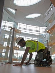 A construction worker put some finishing touches in the glass atrium. ABOVE: Former CEO Tom Ferry.