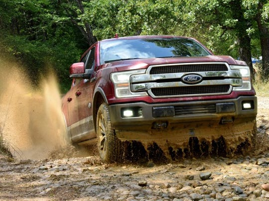 A red 2018 Ford F-150 pickup truck is shown driving through mud.