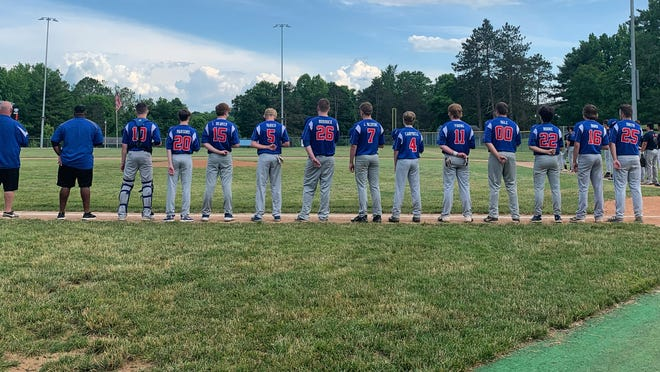 The Cambridge JET Auto Junior team lines up for the playing of the national anthem prior to the start of its home-opening doubleheader against Marietta Monday evening at Don Coss Stadium.