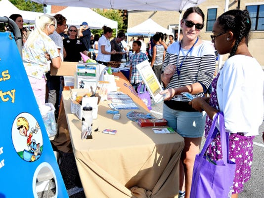 Holly Beistline, back left, of York City Bureau of Health, talks to Azariah Greer, 11, and her sister Mordasha Greer, 10, right, both of York City, about staying hydrated during William Penn Senior High School's back-to-school block party Wednesday. Below, Cyrus Hopkins, 7, left, and Kevon Xapakdy, 11, both of York City, play games at the party.