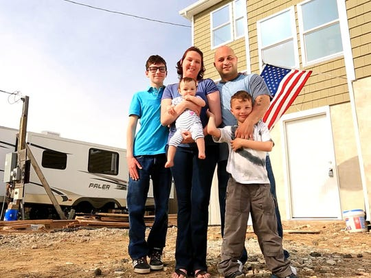 """The Aponte-Kassimatis family stands outside their unfinished home and the trailer they've been living in since superstorm Sandy. In the season finale of the CBS reality show """"The Briefcase"""" the Union Beach family will have to decide what to do with a briefcase full of cash — keep it all or share it with another family in need."""