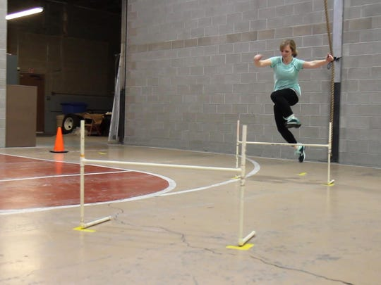 Tribune reporter Andrea Fisher-Nitschke jumps over a hurdle while running the MPAT at the Great Falls Police Department on April 7.