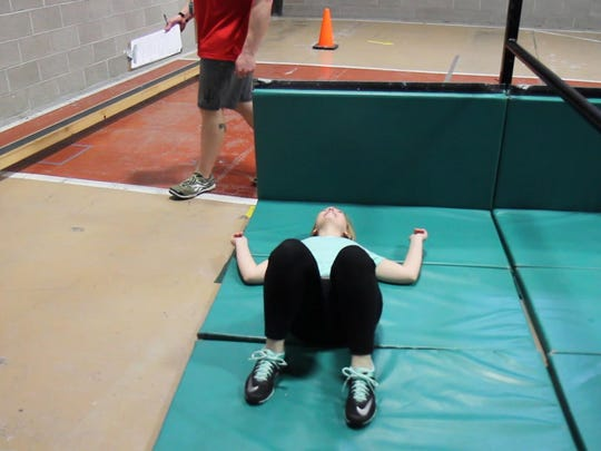 Tribune reporter Andrea Fisher-Nitschke lays on the mat between laps while running the MPAT at the Great Falls Police Dept. on April 7.