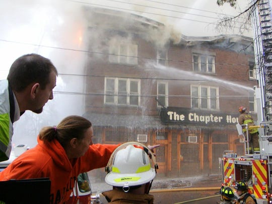 Ann Brust, of Ithaca, who works for CSP Management, center, coordinates with Tom Parsons, chief of the Ithaca Fire Department, Tuesday morning outside The Chapter House. Carol Ann Brust, of Ithaca, who works for CSP Management, center, coordinates with Tom Parsons, the chief of the Ithaca Fire Department Tuesday morning outside The Chapter House