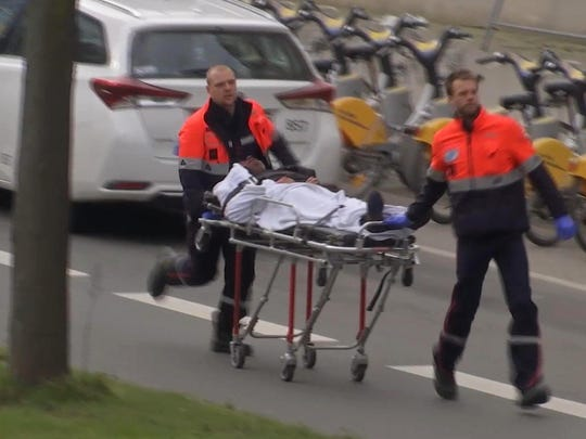 In this image taken from TV an injured person is evacuated as emergency services attend the scene after an explosion in a main metro station in Brussels on Tuesday, March 22, 2016. Explosions rocked the Brussels airport and the subway system Tuesday, killing a number of people and injuring many others just days after the main suspect in the November Paris attacks was arrested in the city, police said. (AP Photo)
