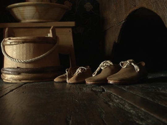 "Two pairs of children's shoes on display inside the ""Birth Room"" at Shakespeare's Birthplace."