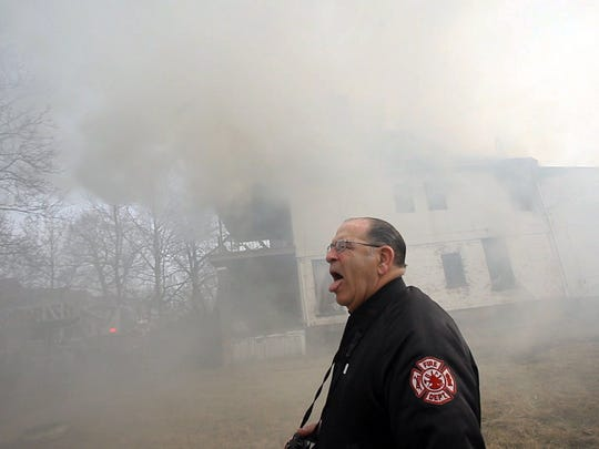 Bill Eisner chokes on smoke while photographing firefighters at work during a blaze on Detroit's west side in 2011. For over 50 years Eisner has been photographing the Detroit Fire Department, amassing hundreds of thousands of photographs in a body of work that has great historical importance.