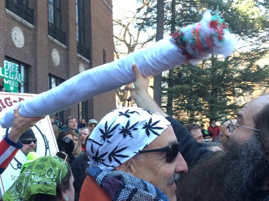 Guitarist Laith Al-Saadi, right, passes a fake joint at the 44th annual Hash Bash on April 4, 2015 in Ann Arbor after playing a Jimmy Hendrix-esque performance of the Star-Spangled Banner on electric guitar. Several thousand people came to the University of Michigan campus in Ann Arbor, where marijuana-legalization advocates encouraged people to take action.