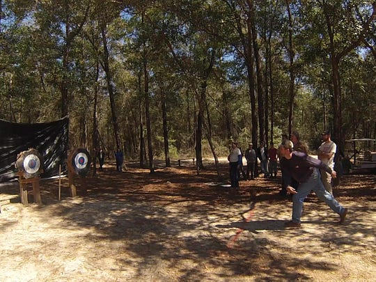 Competitors throw axes and knives at targets Saturday during the Lumberjack Festival.