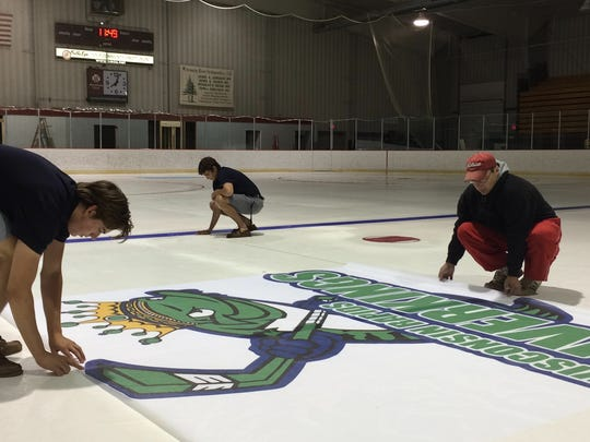 South Wood County Recreation Center rink manager, Jim Arnold, left, gets help with the Wisconsin Rapids RiverKings logo from RiverKings players Eric Arrigo, 17, Chicago, right, and Austyn Quarters, 17, Wisconsin Rapids.