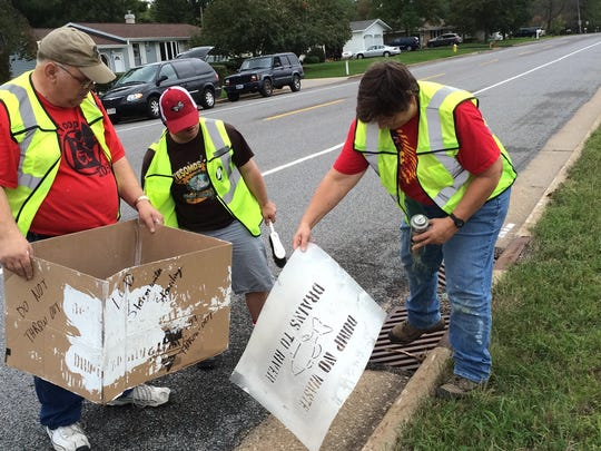 Mark Huser, from left, Nick Cates, and Wendy Cates, prepare to stencil a notice next to a storm drain on First Street South on Saturday.