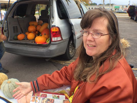 As her husband, Daryl Simonis, unloads pumpkins, Linda Simonis talks about the variety of pumpkins and squash offered for sale at the Wood County Farmers Market in Wisconsin Rapids.