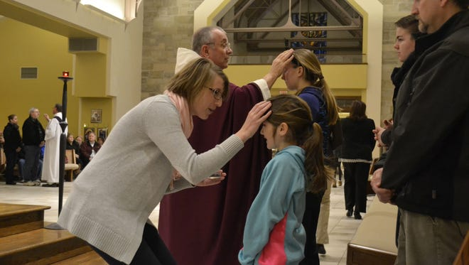 Church pastor the Rev. Tim Shillcox, top center, and catechist Alexa Selner apply ashes on the foreheads of parishioners at an Ash Wednesday service at Our Lady of Lourdes Parish in De Pere.