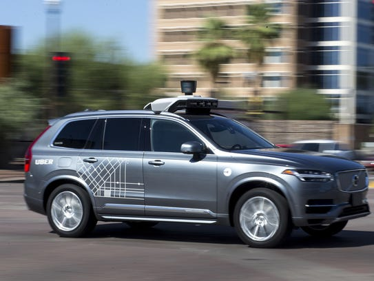 An Uber vehicle cruises in Tempe, Ariz., on Aug. 25,