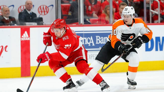 Dylan Larkin protects the puck from Jordan Weal during the first period Tuesday in Detroit.