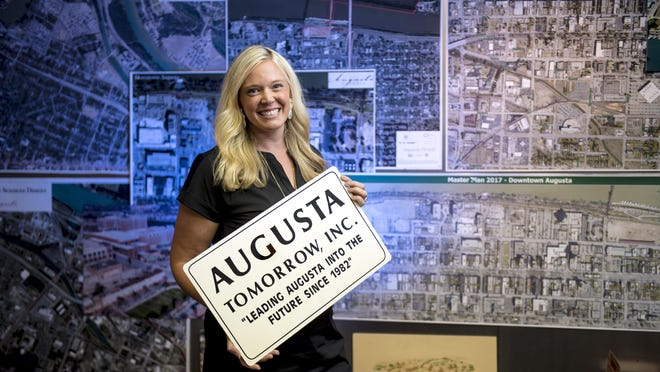 Lauren Dallas, new executive director of Augusta Tomorrow, holds one of the downtown revitalization organization's old signs in front of recent aerial images at its offices in Enterprise Mill in Augusta, Ga., Thursday morning July 16, 2020.