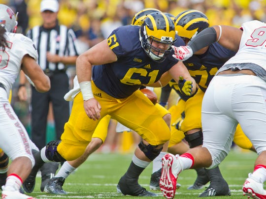 Michigan offensive lineman Graham Glasgow (61) blocks in position in the first quarter of an NCAA college football game against UNLV in Ann Arbor, Mich., Saturday, Sept. 19, 2015.